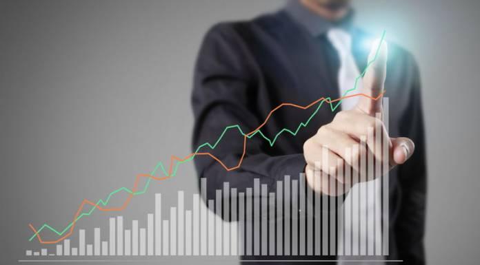 Biznesmen i wykres z tendencją wzrostową jako symbol zysku firmy ze sprzedaży akcji